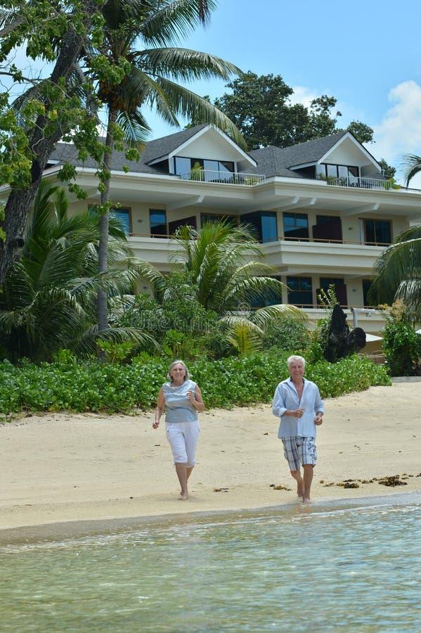 St?ende av ?ldre par som k?r p? den tropiska stranden royaltyfri foto