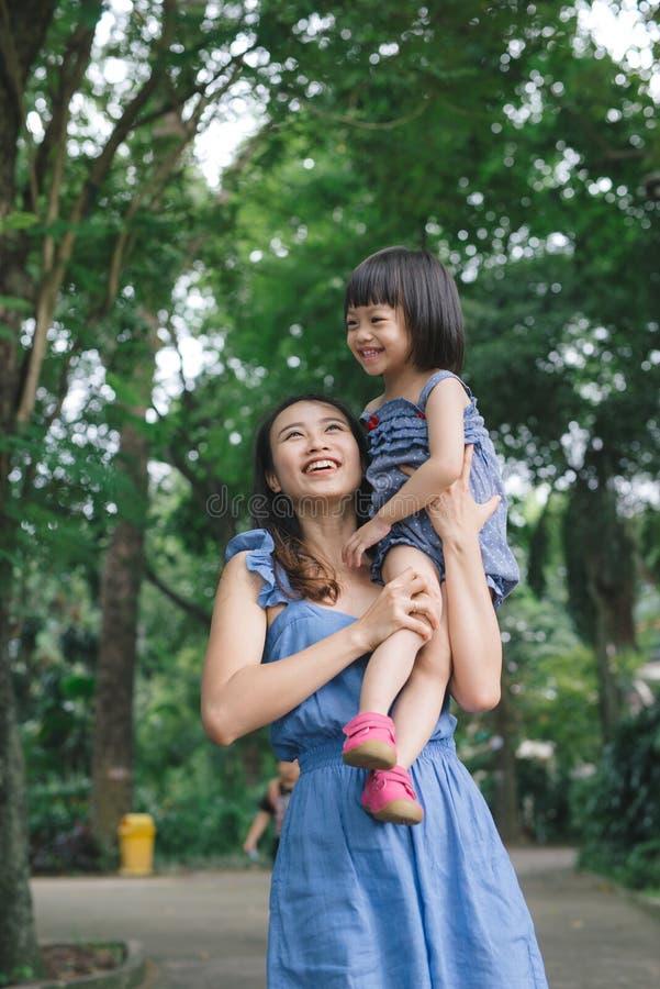St?ende av lilla flickan som kramar hennes mamma med naturen och solljus, familjbegrepp arkivbild