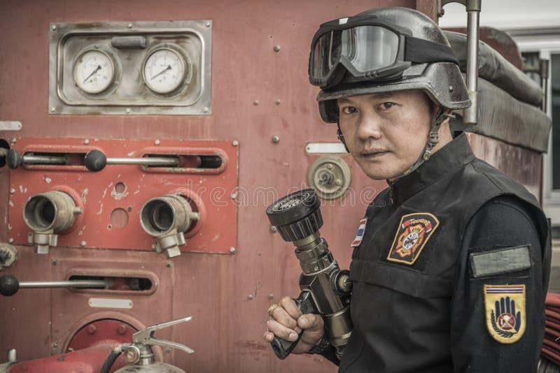 St?ende av lyckliga brandmans lag med utrustning mot lastbilar p? brandstationen arkivfoton