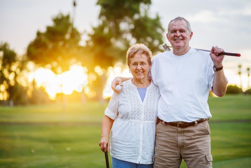 St?ende av lyckliga h?ga par som tycker om den aktiva livsstilen som spelar golf arkivbild
