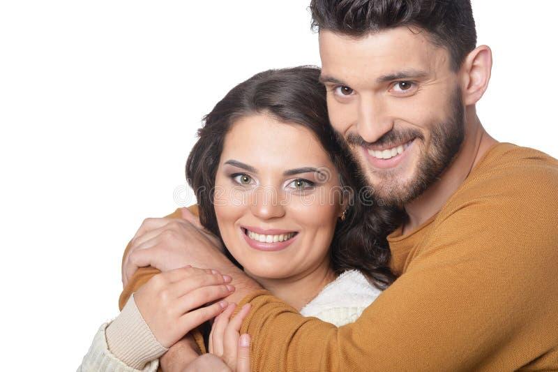 St?ende av lyckliga unga par som ler och kramar p? vit bakgrund royaltyfri bild