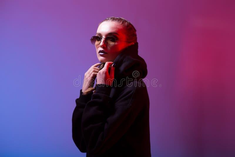 St?ende av modeflickan i en svart tr?ja med en huv- och solglas?gonrundaform i neonljus i studion arkivbilder