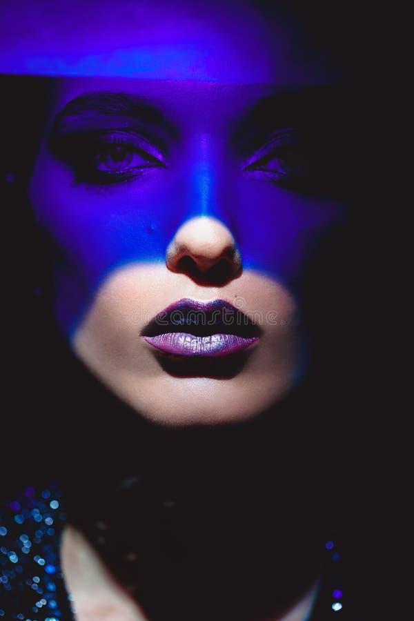 St?ende av modeflickan med stilfull makeup och bl?tt neonljus p? hennes framsida p? den svarta bakgrunden i studion arkivfoton