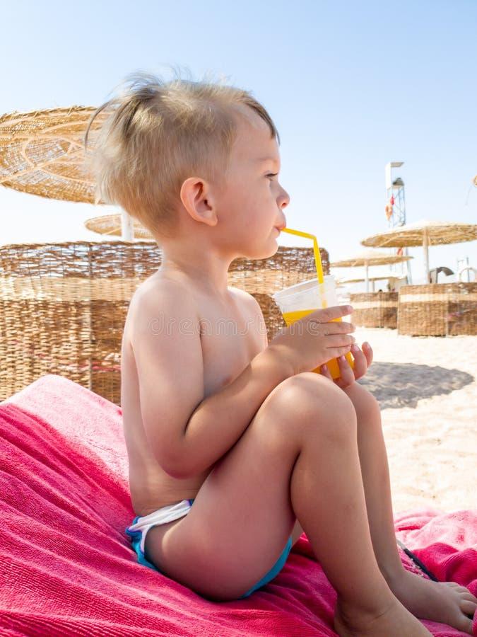 St?ende av pysen som sitter p? havsstranden och dricker orange fruktsaft fr?n sugr?r Barn som kopplar av och har bra royaltyfri bild