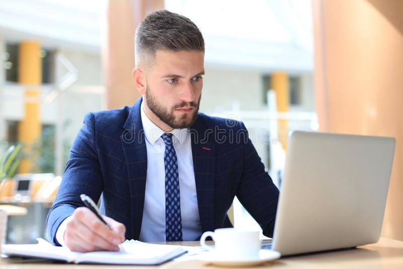 St?ende av sammantr?de f?r ung man p? hans skrivbord i kontoret royaltyfria bilder