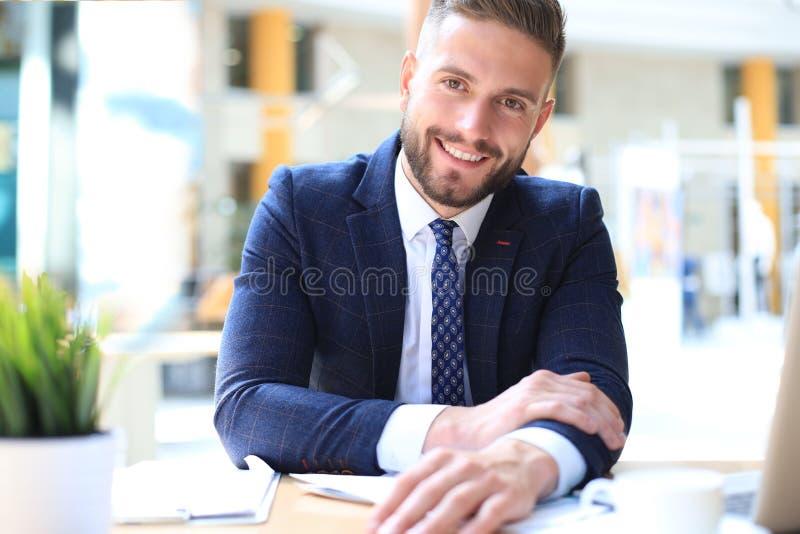 St?ende av sammantr?de f?r ung man p? hans skrivbord i kontoret royaltyfri bild