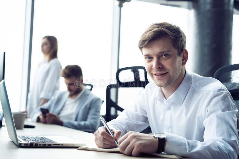 St?ende av sammantr?de f?r ung man p? hans skrivbord i kontoret fotografering för bildbyråer