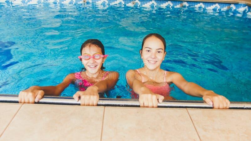 St?ende av tv? lyckliga flickav?nner som inomhus poserar i simbass?ng royaltyfria foton