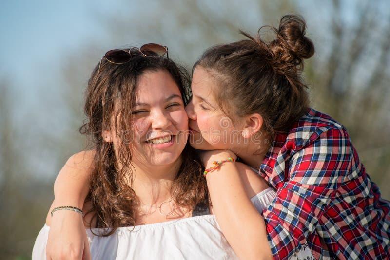 St?ende av tv? lyckliga systrar, utomhus arkivbild