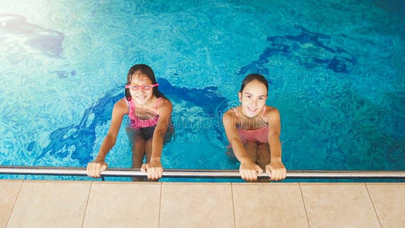 St?ende av tv? v?nner f?r ton?rs- flickor som inomhus simmar och har gyckel i simbass?ng arkivfoton