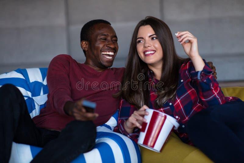 St?ende av unga par som sitter p? soffan som h?ller ?gonen p? en film med uttryck p? deras framsidor royaltyfri bild