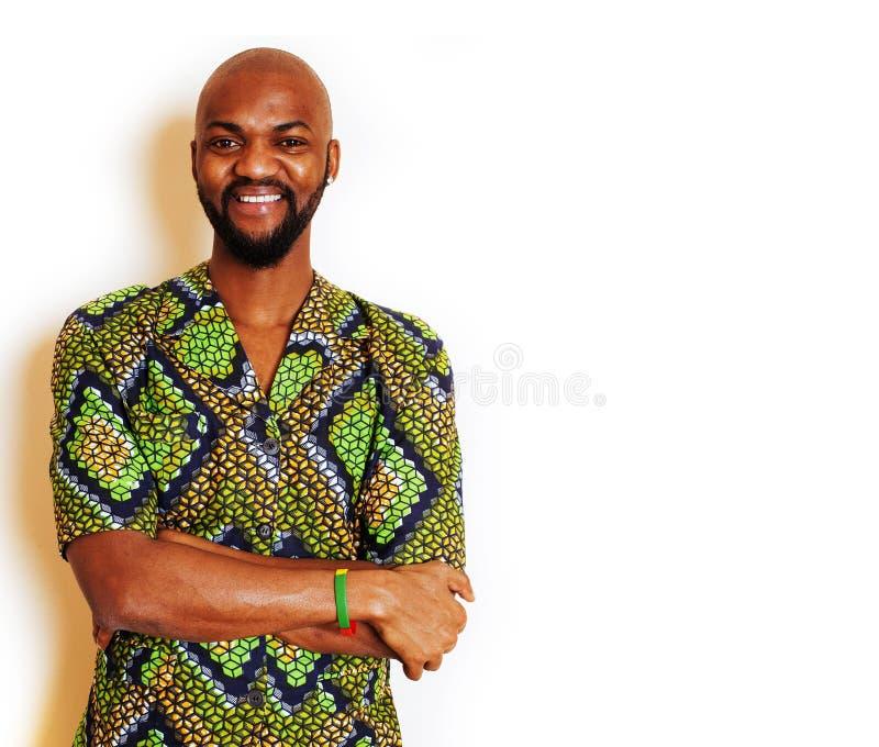 St?ende av ungt stiligt afrikanskt b?ra f?r man som ?r ljust - gr?n nationell dr?kt som ler att g?ra en gest, underh?llningmateri arkivfoto