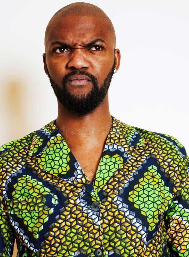 St?ende av ungt stiligt afrikanskt b?ra f?r man som ?r ljust - gr?n nationell dr?kt som ler att g?ra en gest, underh?llningmateri arkivfoton