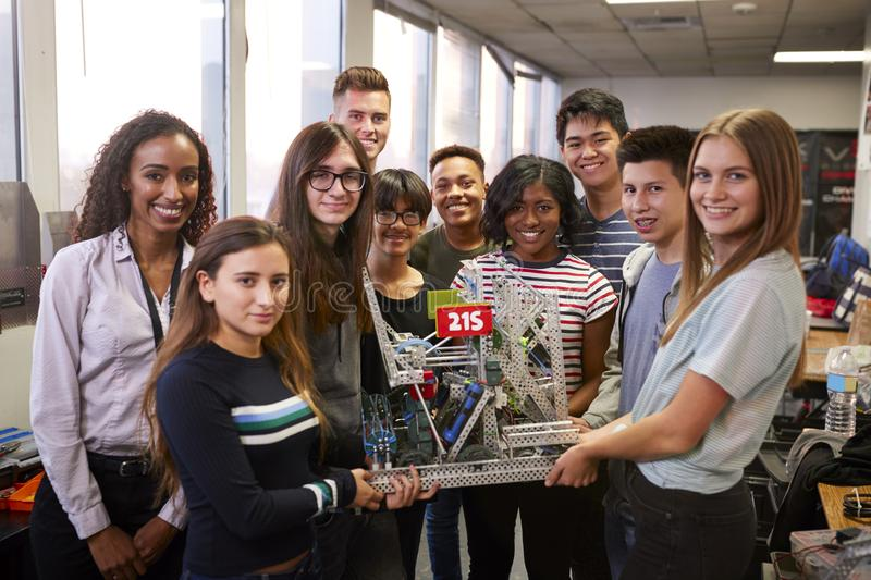 St?ende av universitetsstudenter med l?rareHolding Machine In vetenskap eller robotteknikgrupp royaltyfria foton
