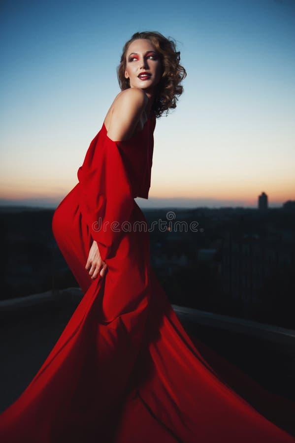 St?ende f?r modemodestil av den unga bed?va kvinnan som poserar i r?d kl?nning i solnedg?ng royaltyfria foton