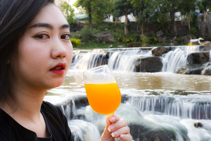 St?endekvinnor r?cker innehavet pressade nytt orange fruktsaft i exponeringsglas med vattenfallbakgrund royaltyfria foton