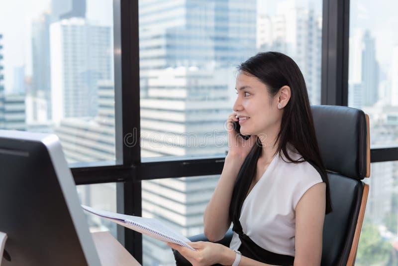 St?enden av aff?rskvinnan talar p? arbetsplats f?r mobiltelefon i regeringsst?llning, den attraktiva h?rliga aff?rskvinnan talar  arkivbild