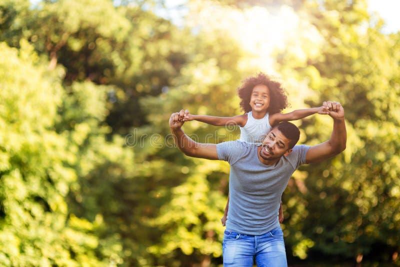 St?enden av barn avlar att b?ra hans dotter p? hans baksida royaltyfria bilder
