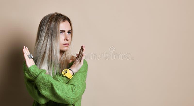St?enden av den allvarliga, olyckliga s?kra blonda kvinnan som rymmer tv? armar, korsade och att g?ra en gest inget tecken som bo arkivbild