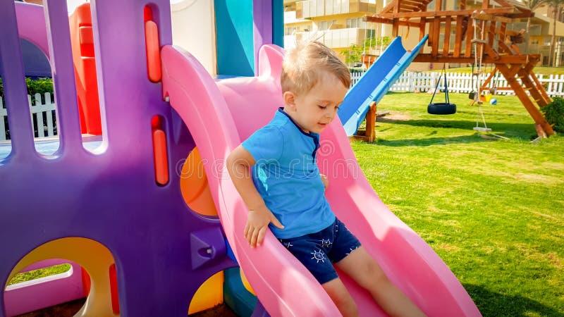 St?enden av den lyckliga le litet barnpojkeridningen p? f?rgrik plast- glidbana p? barnlekplats p? parkerar royaltyfria foton