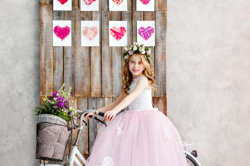 St?enden av en h?rlig liten flicka i en krans av nya blommor p? hennes huvud sitter p? en cykel i en frodig rosa kl?nning lycklig arkivfoto