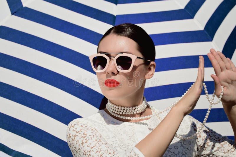 St?enden av en n?tt ung kvinna i vit sn?r ?t kl?nningen, den vit p?rlemorf?rg halsbandet och ljust - rosa solglas?gon arkivbild