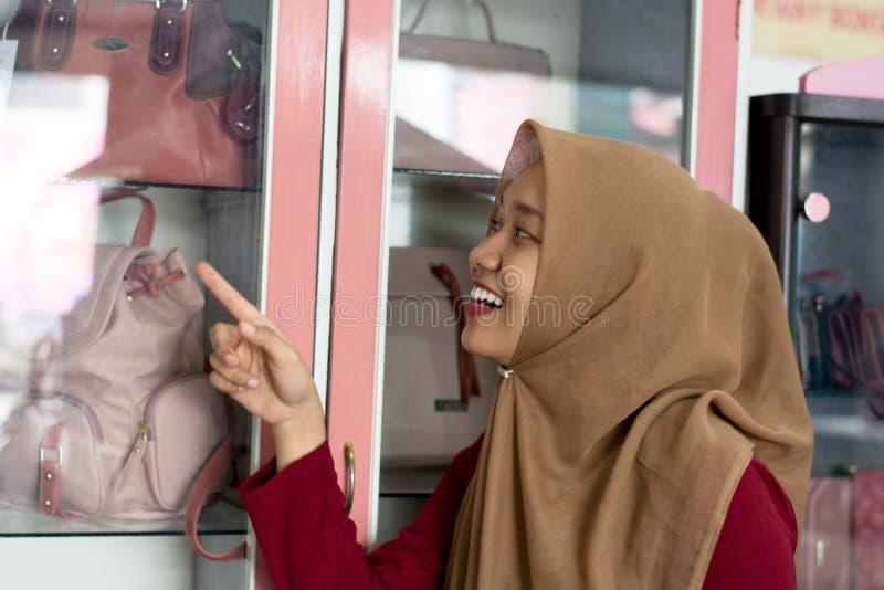 St?enden av en ung muslim dr?kt som pekar p? handv?skap?sen inom exponeringsglas, st?ller ut arkivbilder