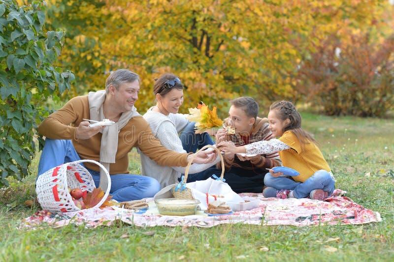 St?enden av familjen som har en picknick i, parkerar i h?st arkivfoton