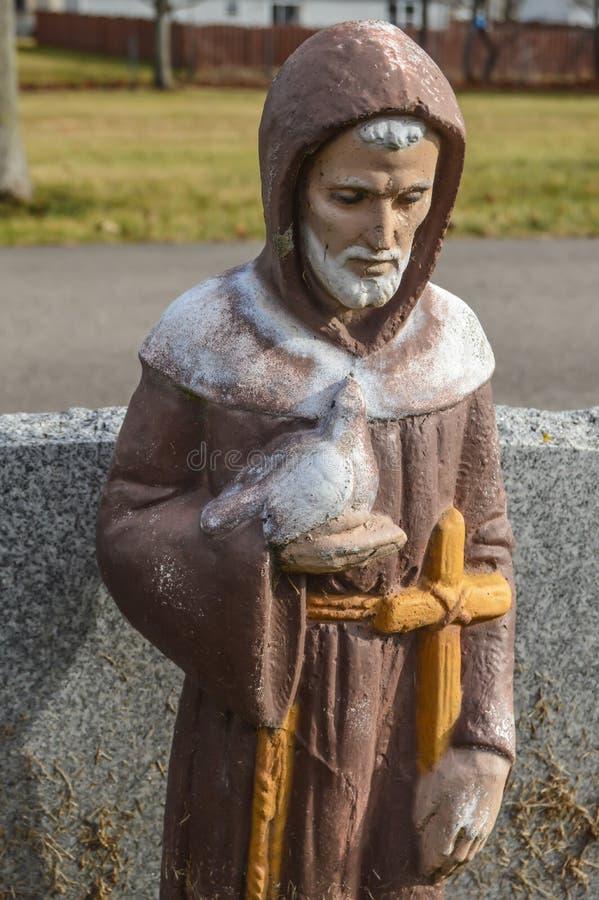 St Francis av den Assisi statyn som rymmer en duva och ett kors royaltyfri foto