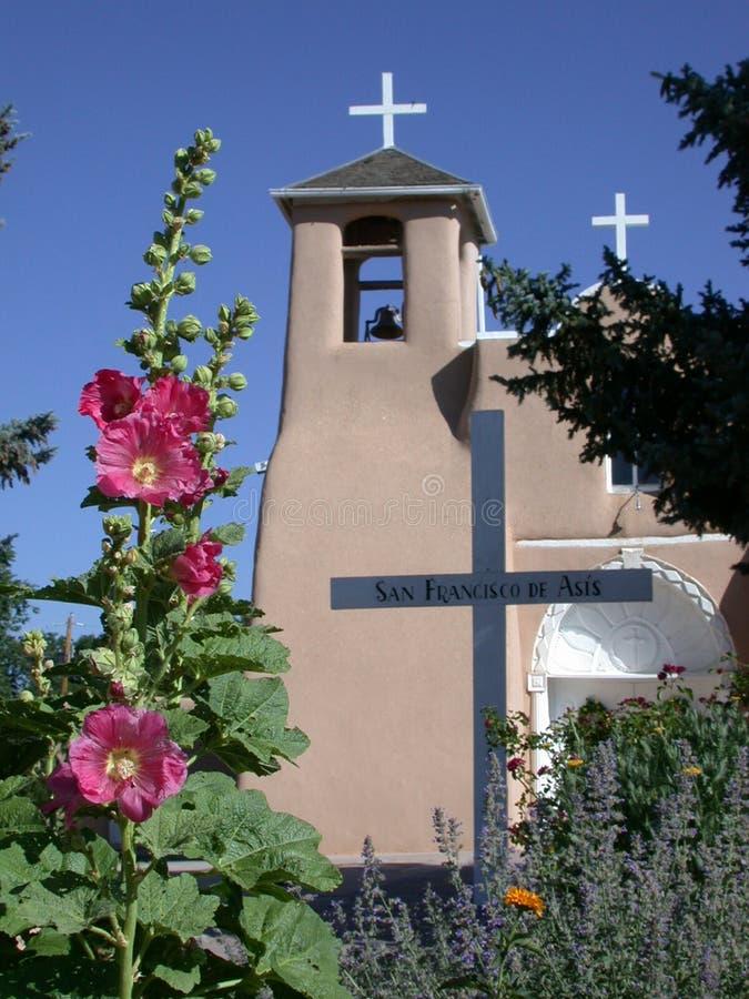 St Francis della chiesa cattolica di Asisi con i Hollyhocks fotografia stock