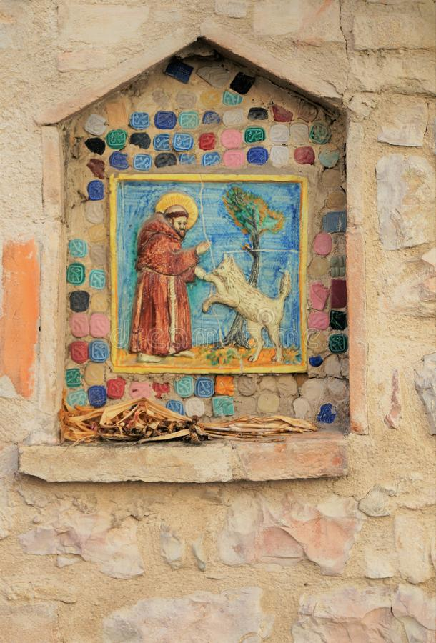 St. Francis Shrine in Assisi. A small handmade tile mosaic shrine to Saint Francis embedded in a medieval stone wall in Assisi. Founder of the Franciscan Order royalty free stock images