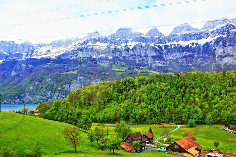 St Gallen view Switzerland. Farmhouses above lake Walensee on green spring valley on the foot of Alps mountains, Switzerland.Photo taken on May 3rd,2017 stock photos