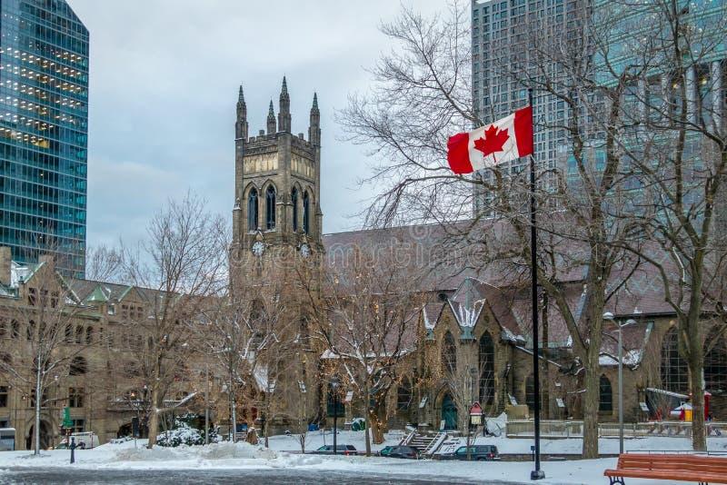 ST George ` s Αγγλικανική Εκκλησία στην πλατεία του Καναδά με τη σημαία - Μόντρεαλ, Κεμπέκ, Καναδάς στοκ εικόνα