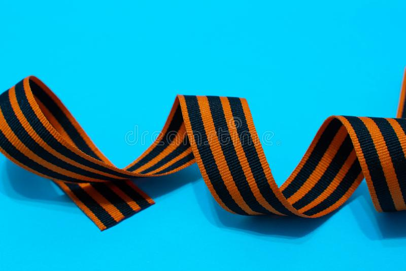 St. George`s ribbon on blue background. The symbol of the great victory of May 9 royalty free stock photo