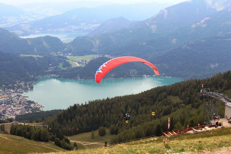 St Gilgen, Австрия: Красный параплан летая над горами стоковое изображение rf