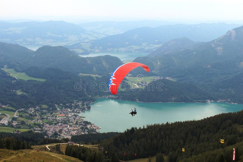 St Gilgen, Австрия: Красный параплан летая над горами стоковая фотография rf
