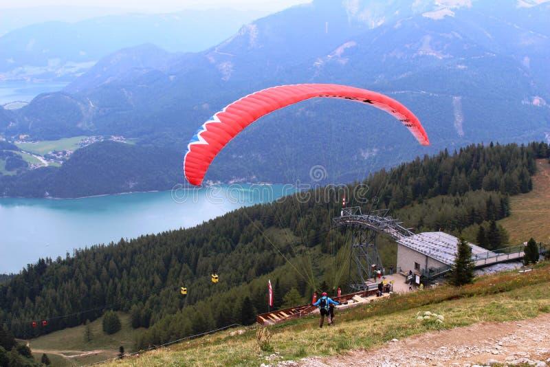St Gilgen, Австрия: Красный параплан начинает свой полет над горами стоковые фотографии rf