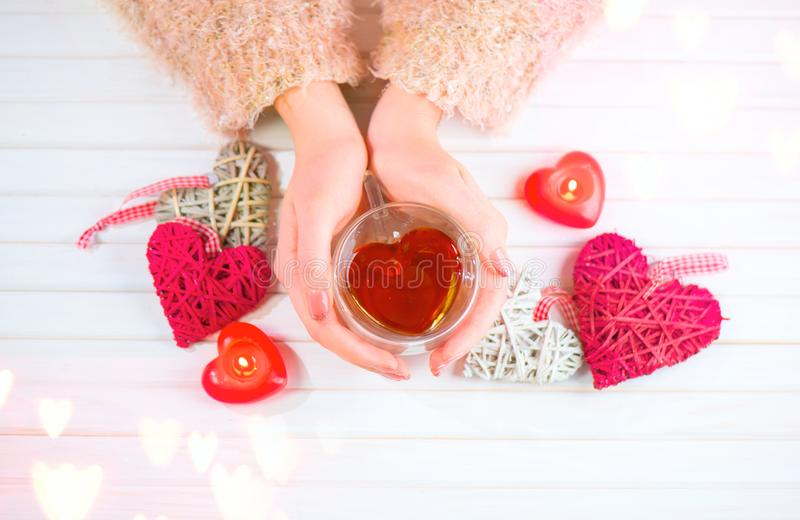 St Giorno del ` s del biglietto di S La giovane donna passa la tazza di tè a forma di cuore della tenuta sopra fondo di legno immagini stock libere da diritti