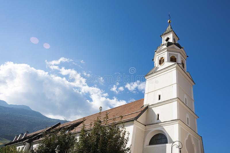 St Gotthard and St Erhard church, Bressanone Brixen, italy. White tower of St Erhard church Brixen Bressanone, Italy. Sunny day and blue sky. copy space royalty free stock images