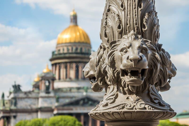 St Isaac& x27; 在焦点外面的s大教堂,在前景狮子雕塑在杆,圣彼德堡,俄罗斯的 免版税库存照片