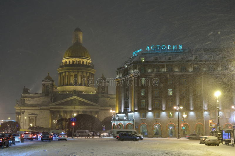 St. Isaac's Cathedral and the Astoria hotel with the falling sno royalty free stock photos