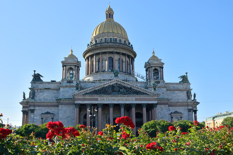 St. Isaac's Cathedral on a background of red roses on the square bright Sunny day under blue sky stock image