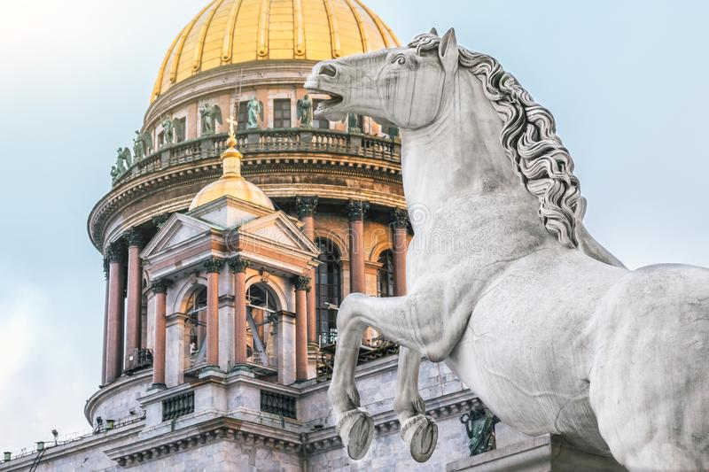 St. Isaac`s Cathedral gold dome and statues of stone horse. stock photo