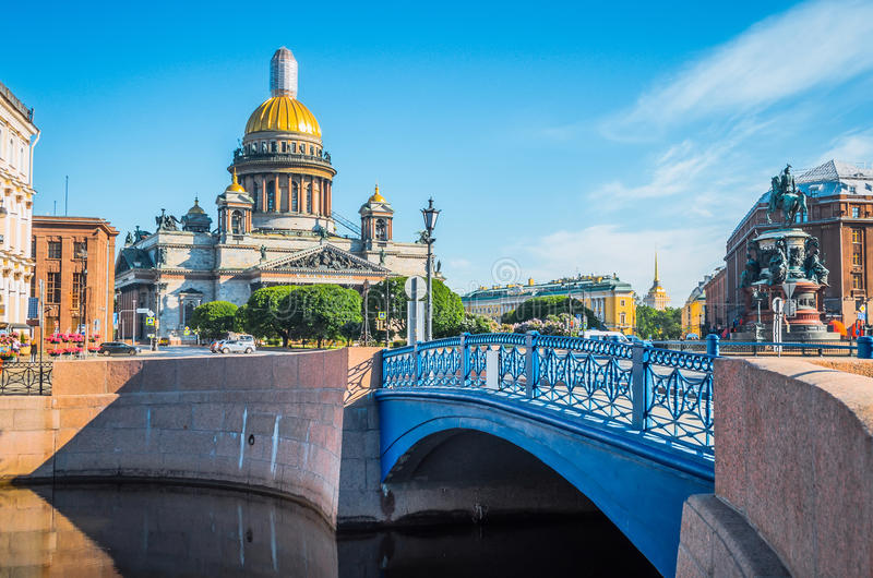 St. Isaac`s Cathedral in the morning in the summer, and a view of the river and blue bridge. St. Isaac`s Cathedral in the morning in the summer, and a view of royalty free stock image