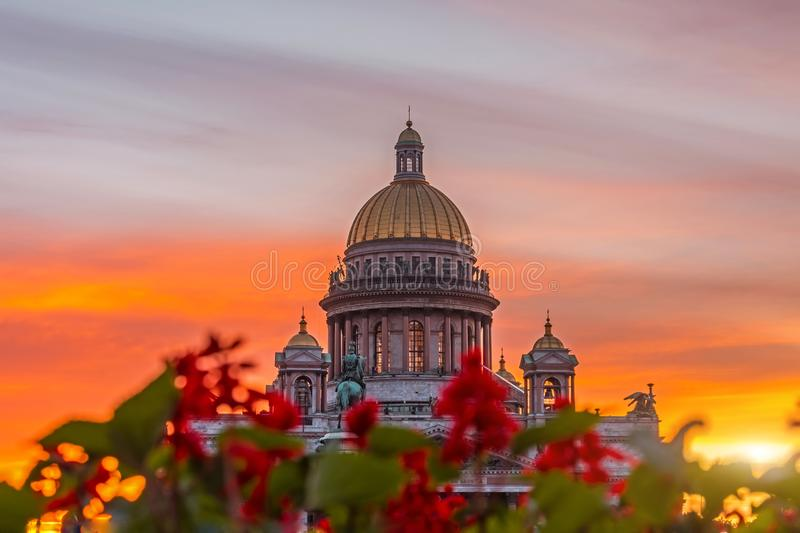 St. Isaac`s Cathedral in the square, in St. Peterburg in the evening on a bright orange sunset sky, in the foreground red flowers stock photos