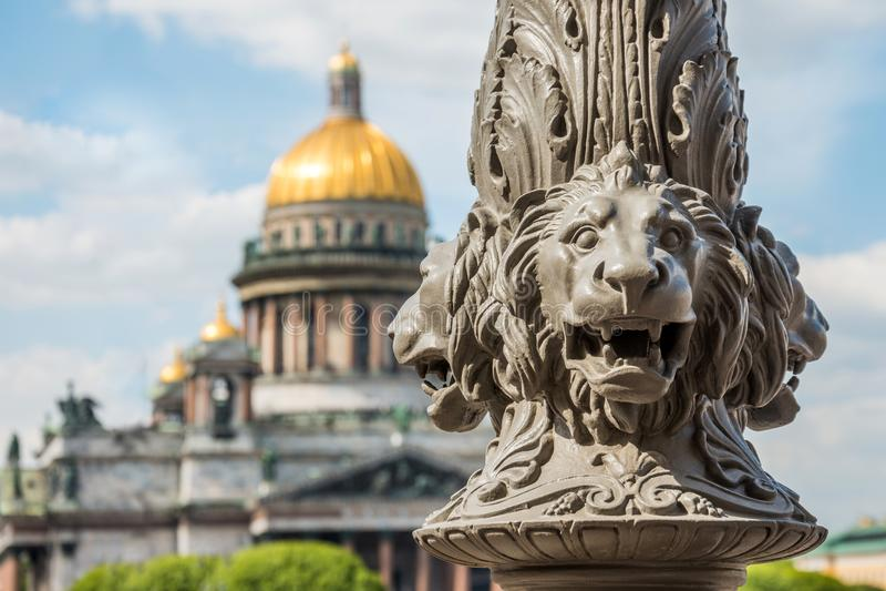 St Isaac& x27; s-domkyrka ut ur fokus, i förgrunden skulpturen av lejon på en pol, St Petersburg, Ryssland royaltyfri foto