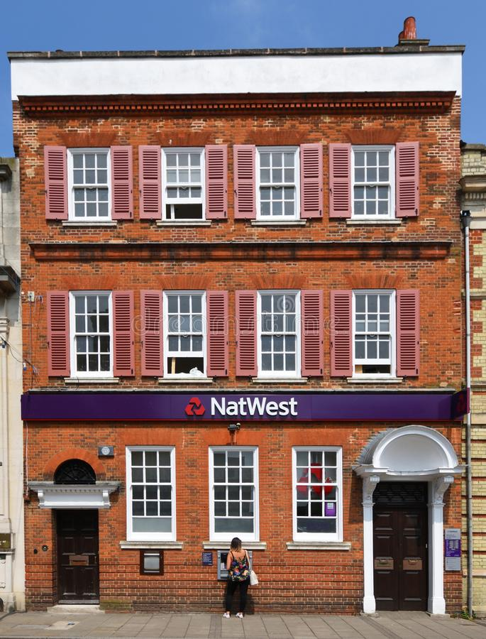Woman using ATM at Natwest bank St Ives Cambridgeshire England. royalty free stock images