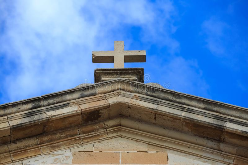 St John Baptist chapel in Malta. White cross on the top of a limestone building. Blue sky with clouds background. royalty free stock photo