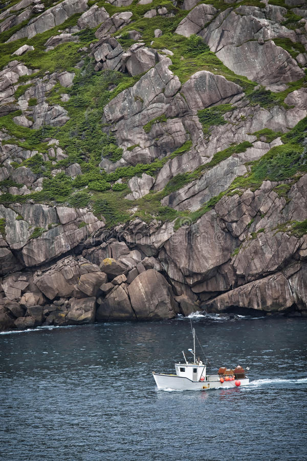 St. John's, Newfoundland. Fishing boat laded with crab traps sailing into St. John's Harbour past Signal Hill, Newfoundland stock image