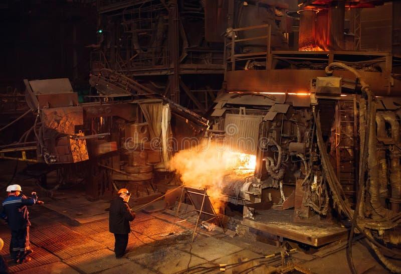 St?l f?r v?xt f?r tillverkning av En elektrisk smältningspanna Fabriksarbetaren tar en pr?vkopia f?r metall arkivfoto